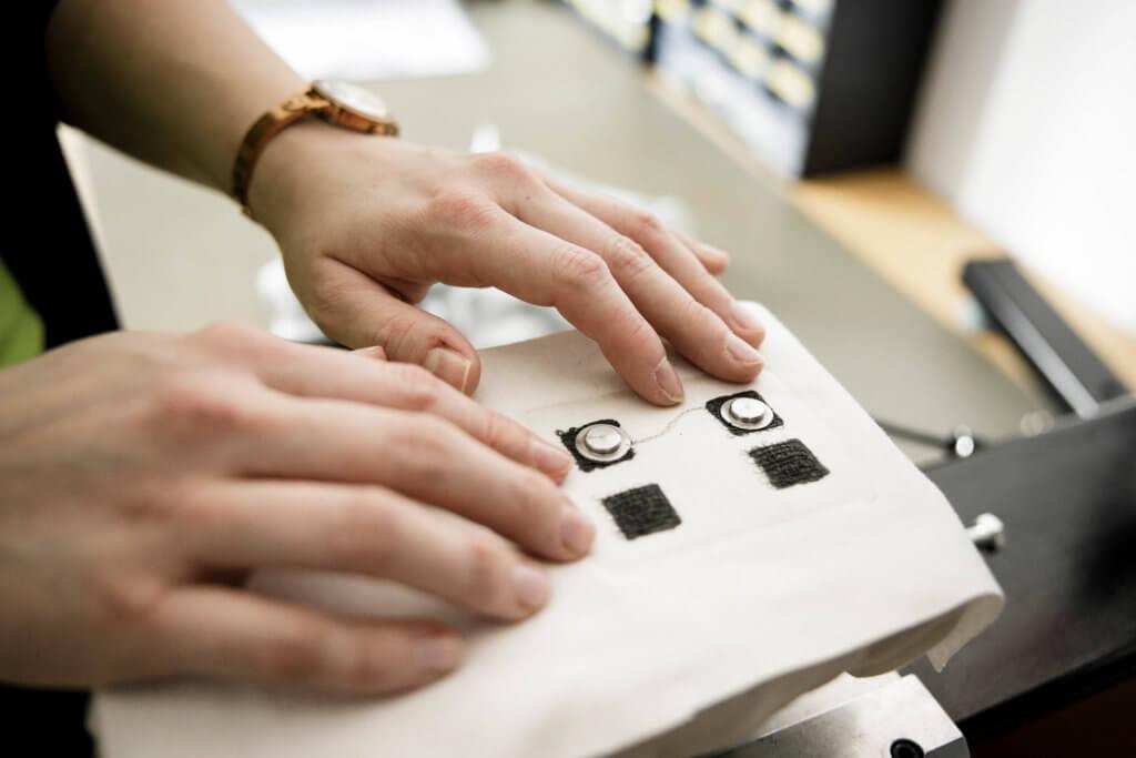 Bild von zwei Händen auf einem Smart-Textile-Stoff