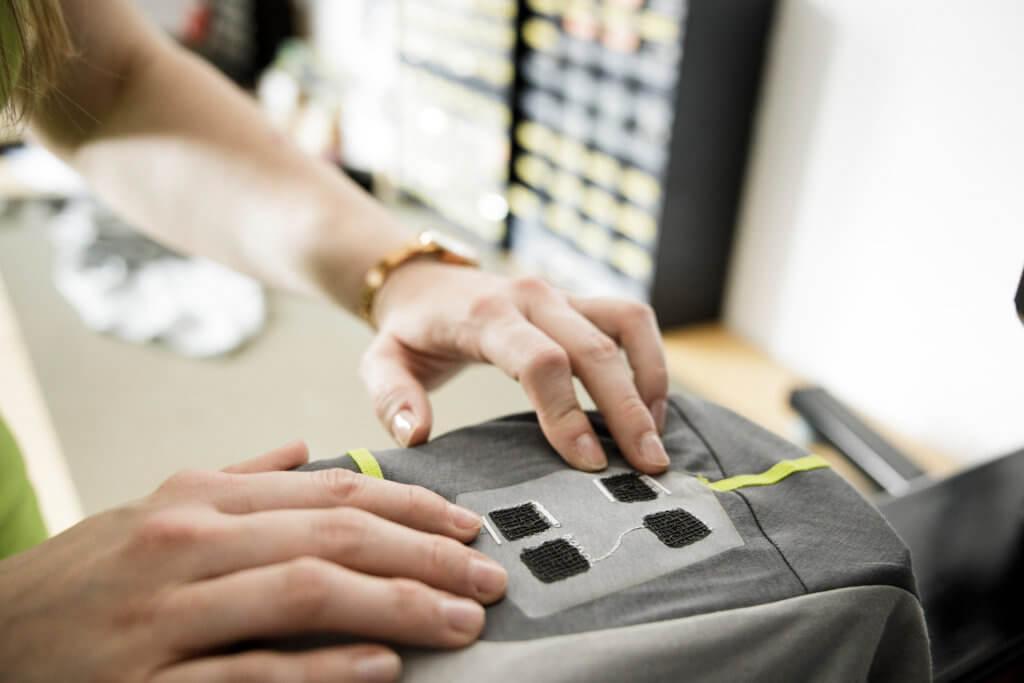 Bild von zwei Händen, die ein Smart Textile-Element positionieren