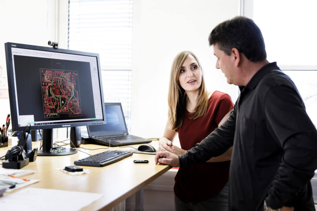 Bild von zwei Mitarbeitern in Diskussion vor einem Bildschirm