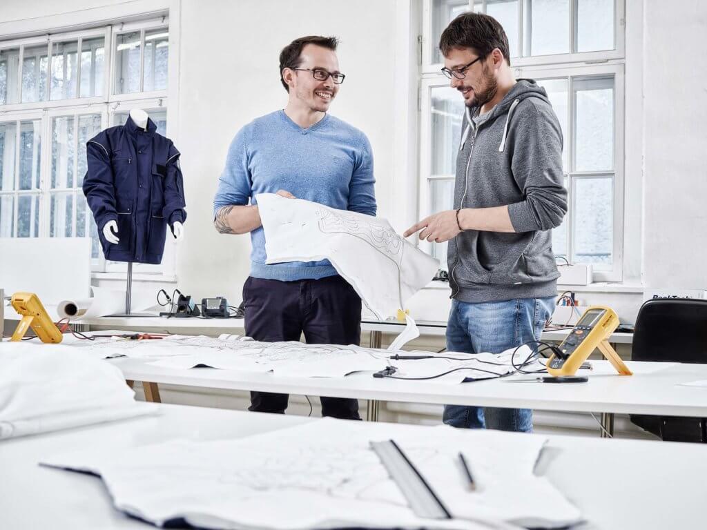 Bild mit zwei Personen an einem Textilarbeitsplatz